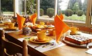 petit déjeuner à base de produits frais maison, servi dans la véranda donnant sur le parc
